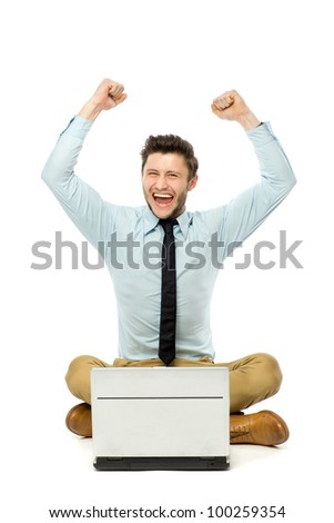 Man sitting with laptop with arms raised - stock photo