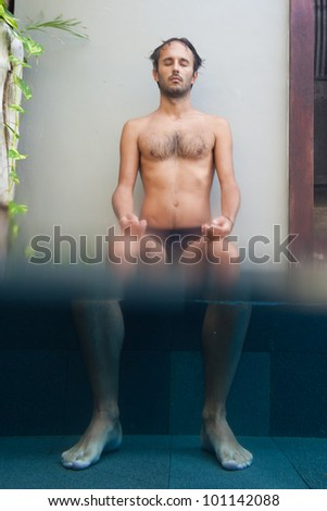 Man sitting with magnified feet in pool. - stock photo