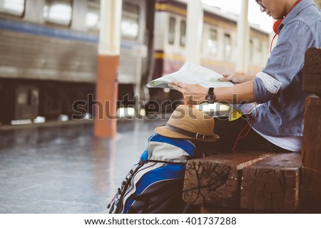 man sitting with map. travel bag at the train station.vintage filter effected . - stock photo