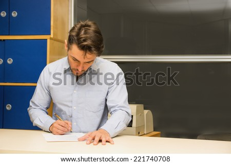 Man sitting working in an office concentrating looking down while writing with a pen on a sheet of paper