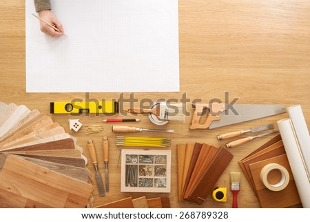 Man sketching a DIY project on a work table with construction tools top view, hobby and crafts concept - stock photo