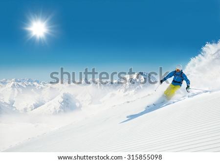 Man skier running downhill on sunny alpine slope - stock photo