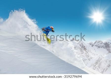 Man skier running downhill on sunny Alps slope - stock photo