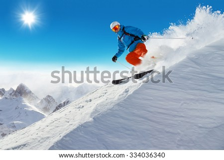 Man skier running downhill on sunny Alps slope - stock photo
