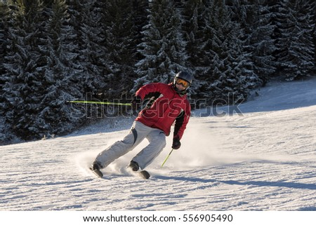 Man skiing on a slope of winter resort in the mountains on beautiful sunny day