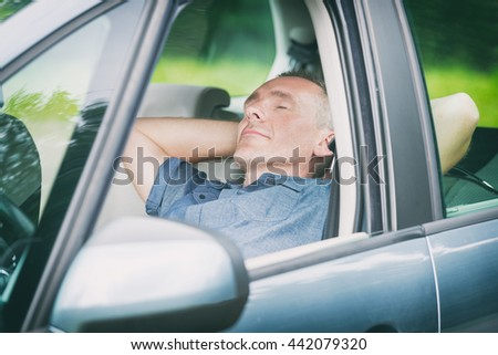 Man sleeping in the car before next part of the journey - stock photo