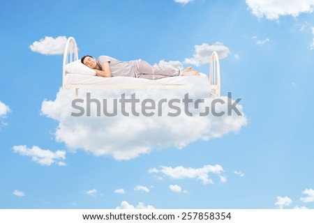 Man sleeping on a bed in the clouds high up in the sky - stock photo