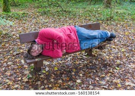 Man sleeping on a bench in a forest in autumn