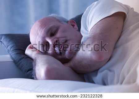 man sleeping on his couch in a white living room - stock photo