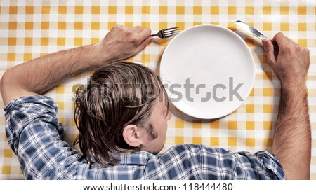 Man sleeping on the table with a empty plate - stock photo