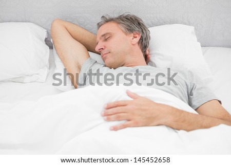 Man sleeping soundly in his bed at home - stock photo