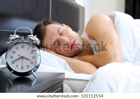 Man sleeping with alarm clock in foreground - stock photo