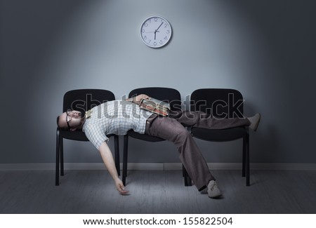 Man sleeps in a waiting room chairs - stock photo