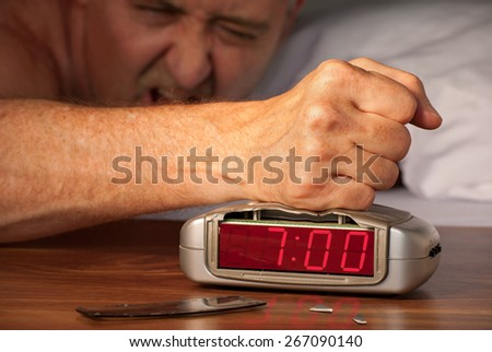 Man smashing alarm clock because he is angry at the alarm buzzer because of hangover, insomnia, work stress or snoring spouse. - stock photo