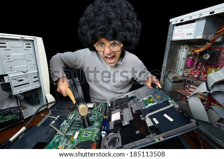 man smashing laptop with hammer - stock photo