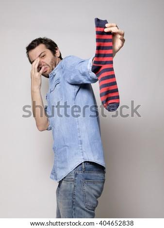 Man smelling a stinky sock - stock photo