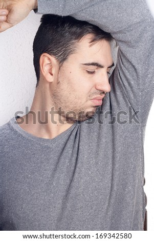 man smelling armpit - stock photo