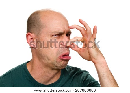 Man smells something stinky and pinches his nose to stop the bad odor. - stock photo