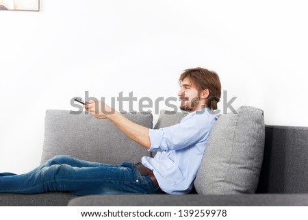 man smile watching tv hold remote control, young happy guy sitting, couch sofa in living room at home, with copy space