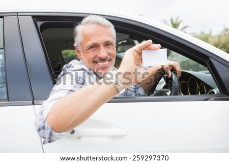 Man smiling and holding card in his car - stock photo