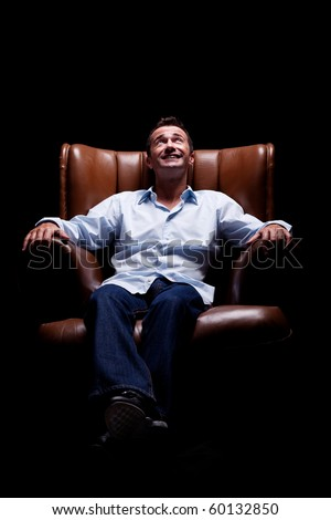 Man smiling and looking up seated on a chair, isolated on black, studio shot