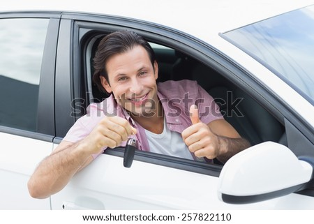 Man smiling and showing key in his car - stock photo