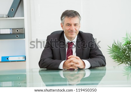 Man smiling and sitting in his office with his hands folded