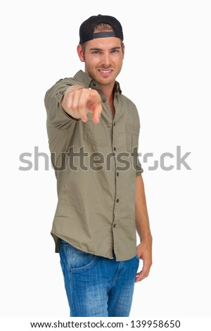 Man smiling and wearing baseball hat backwards and pointing on white background - stock photo
