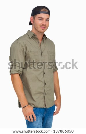Man smiling and wearing baseball hat backwards on white background - stock photo