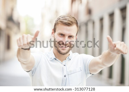 Man smiling at camera showing thumbs up  - stock photo