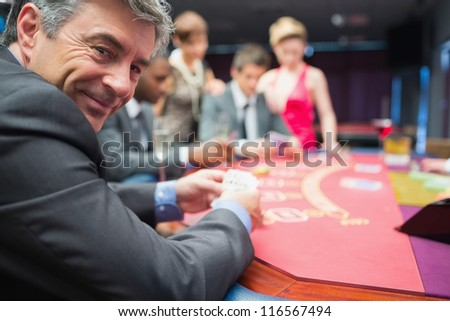 Man smiling at the poker table in casino - stock photo