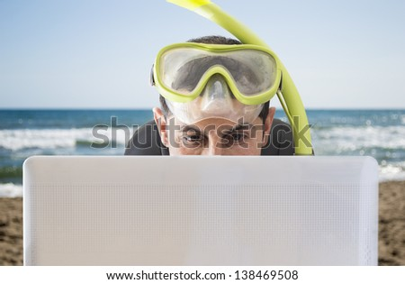 Man smiling at web prices for your holidays and trips on the beach - stock photo