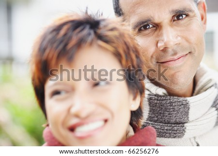 Man smiling for the camera beside his girlfriend - stock photo