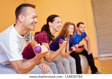 Man smiling in fitness class with dumbbells in a health club - stock photo