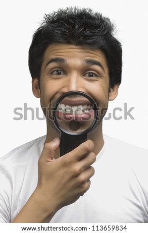 Man smiling in front of a magnifying glass - stock photo