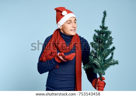 man smiling looking at the Christmas tree on a blue background, studio