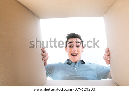 Man smiling, unpacking and opening carton box, and looking inside - stock photo