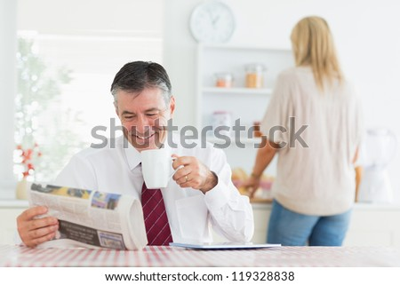 Man smiling while reading newspaper before work in kitchen drinking coffee - stock photo