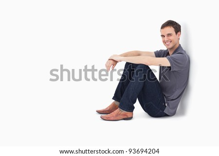 Man smiling while sitting against a wall with white background - stock photo