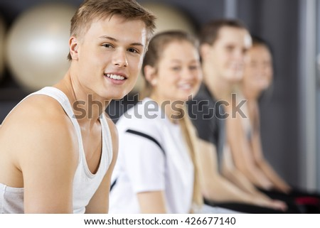 Man Smiling While Sitting With Friends In Gym - stock photo
