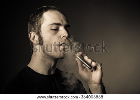 Man smokes electronic cigarette on dark background.