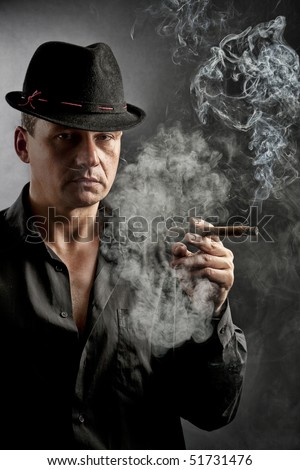Man smoking a cigar. Dark background.