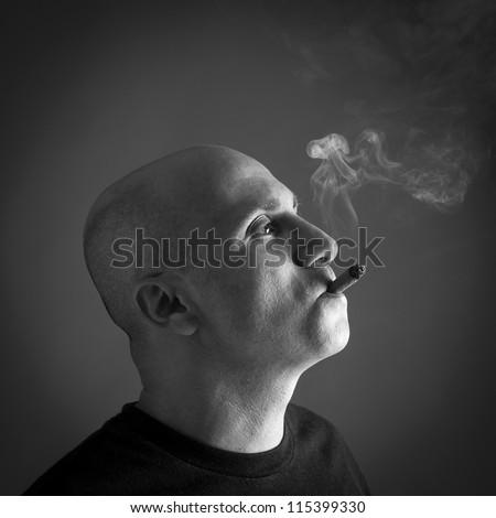 Man smoking cigar portrait on dark background. Black and white image. - stock photo