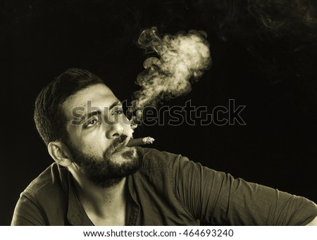 Man Smoking Cigar surrounded by Smoke / short bearded man with a gangster look smoking cigar surrounded by smoke over dark background