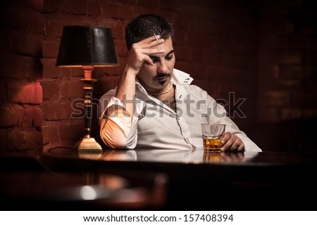 Man smoking cigarette and drinking whiskey in bar