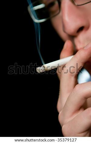 Man smoking cigarette over black - stock photo