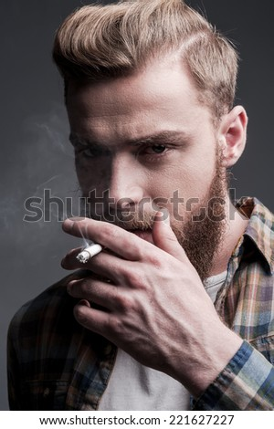Man smoking. Handsome young bearded man smoking a cigarette and looking at camera while standing against grey background