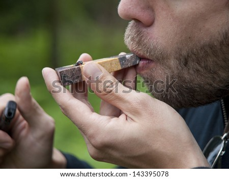 Man smoking marijuana pipe - stock photo