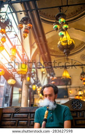 Man smoking turkish hookah in the cafe with coloful lamps on background in Istanbul, Turkey - stock photo