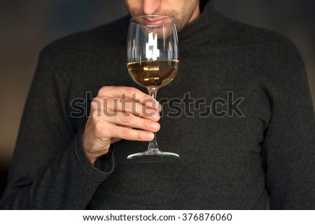Man sniffing white wine in a glass, close up